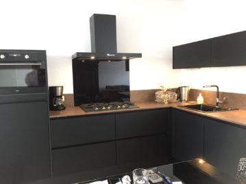 Onze greeploze matzwarte lakkeuken met zwarte afzuigkap, zwarte oven en zwarte kookplaat is in combinatie met het 2 cm dikke werkblad met spatranden in koperkleur. Keuken gekocht in Sittard bij I-Kook Keukenmatch