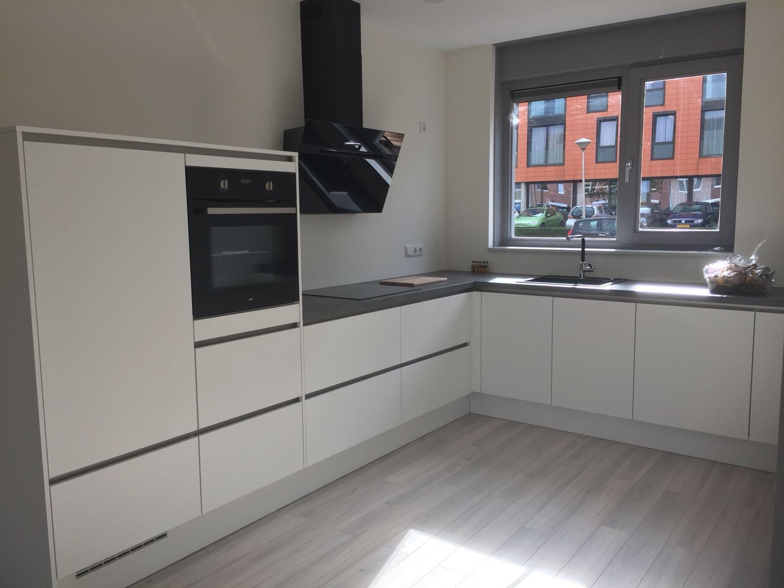 greeploze alpine witte L-keuken, werkblad beton schiefer grijs, Veel lades. Schuine afzuigkap, ideaal voor langere mensen, zwarte apparatuur