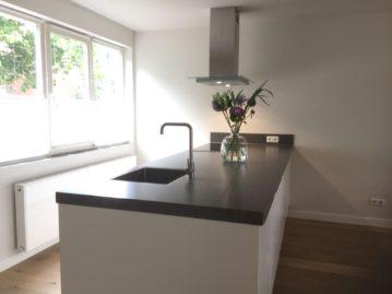 keuken gekocht bij I-Kook SIttard, Keukenmatch, witte moderne keuken, groot keukeneiland, houten schuifdeur