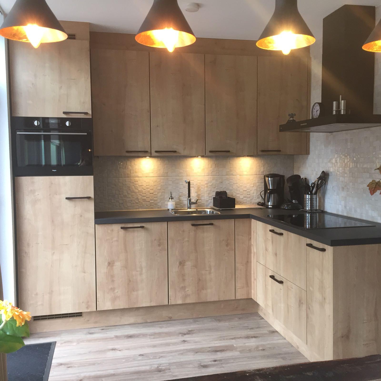 Een houtfronten keukenpaneel gecombineerd met een zwart werkblad in een L-vormige keuken. Keuken gekocht in Sittard bij Keukenmatch